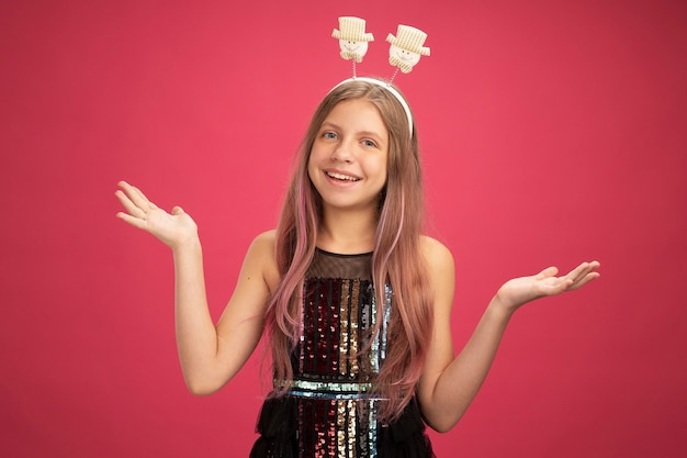 Little girl in glitter party dress looking at camera with happy face smiling cheerfully new year celebration holiday concept standing over pink background