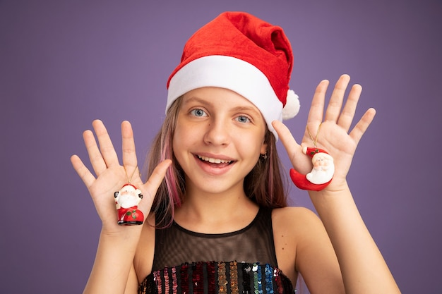 Little girl in glitter party dress and santa hat holding christmas toys looking at camera with happy face smiling cheerfully standing over purple background