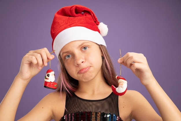 Little girl in glitter party dress and santa hat holding christmas toys looking at camera with sad expression pursing lips standing over purple background