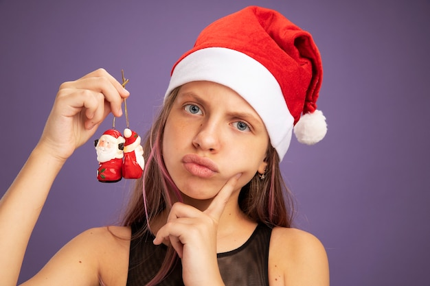 Little girl in glitter party dress and santa hat holding christmas toys looking at camera with serious face standing over purple background
