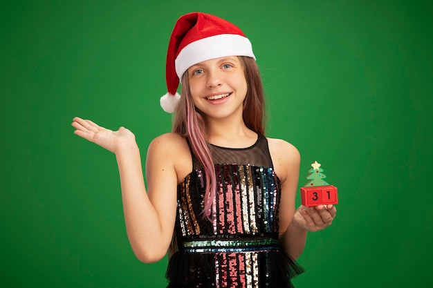 Little girl in glitter party dress and santa hat holding toy cubes with new year date looking at camera smiling cheerfully with arm raised standing over green background