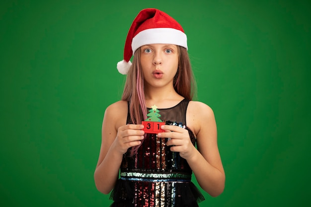 Little girl in glitter party dress and santa hat holding toy cubes with new year date looking at camera surprised standing over green background