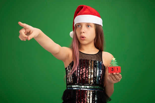 Little girl in glitter party dress and santa hat holding toy cubes with new year date looking at something surprised pointing with index finger to the side standing over green background
