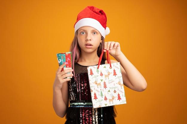 Bambina in abito da festa glitter e cappello da babbo natale con in mano due bicchieri di carta colorati e un sacchetto di carta con regali guardando la telecamera sorpresa in piedi su sfondo arancione orange