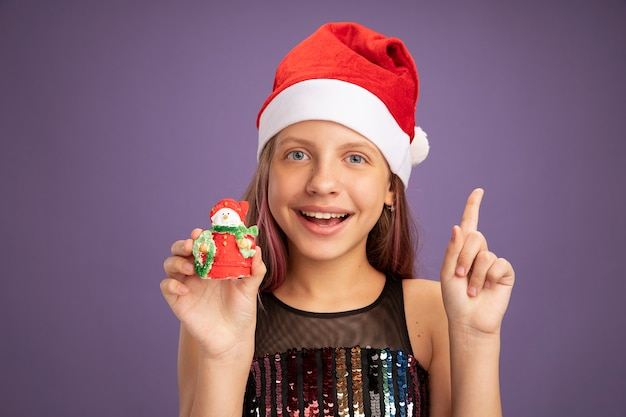 Little girl in glitter party dress and santa hat showing christmas toy looking at camera happy and surprised showing index finger standing over purple background