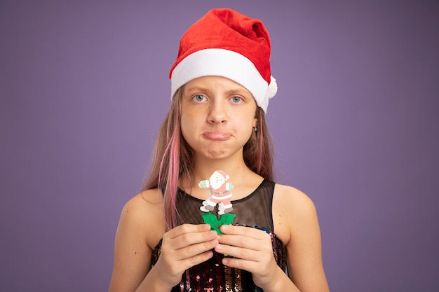 Bambina in abito da festa glitterato e cappello da babbo natale che mostra un giocattolo di natale che guarda la telecamera con un'espressione triste che increspa le labbra in piedi su sfondo viola purple