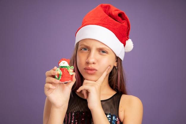Bambina in abito da festa glitterato e cappello da babbo natale che mostra il giocattolo di natale che guarda l'obbiettivo con espressione scettica in piedi su sfondo viola