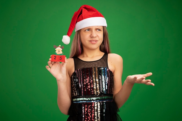 Little girl in glitter party dress and santa hat showing toy cubes with date twenty five looking aside confused and displeased raising hand in displeasure standing over green background