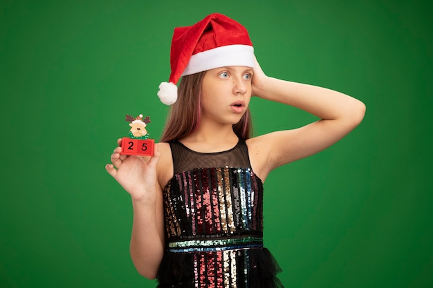 Little girl in glitter party dress and santa hat showing toy cubes with date twenty five looking aside surprised standing over green background