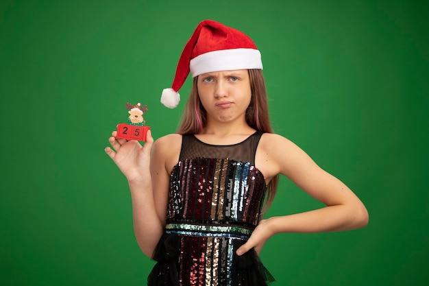 Little girl in glitter party dress and santa hat showing toy cubes with date twenty five looking at camera displeased standing over green background