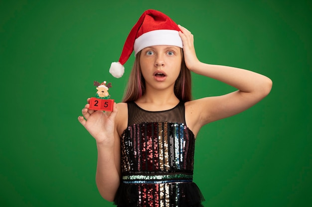 Little girl in glitter party dress and santa hat showing toy cubes with date twenty five looking at camera surprised and amazed with hand on her head standing over green background