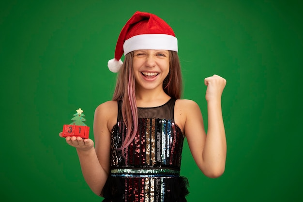 Little girl in glitter party dress and santa hat showing toy cubes with new year date clenching fist happy and excited standing over green background