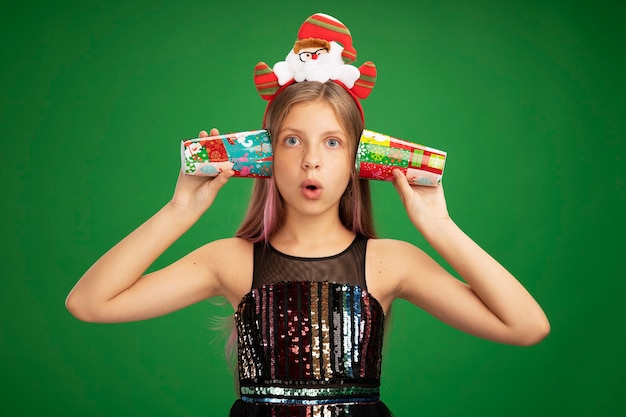Little girl in glitter party dress and santa headband holding colorful paper cups over her ears looking surprised standing over green background