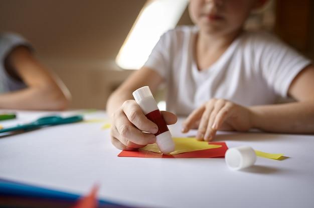 Маленькая девочка клеит цветную бумагу на столе, малыш в мастерской. урок творчества в художественной школе. молодой художник, приятное хобби, счастливое детство