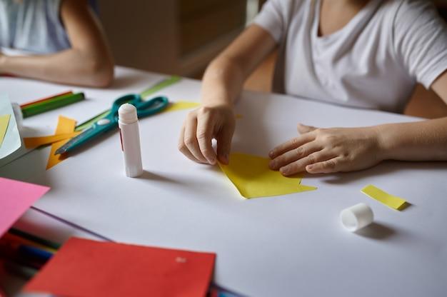 Маленькая девочка клеит цветную бумагу, ребенок в мастерской