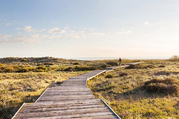 Маленькая девочка идет по променаду на берегу моря на рассвете