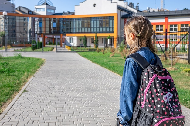 Little girl goes to the elementary school. child with a backpack is going to study. back to school concept.