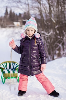 Little girl goes sledding on a warm winter day