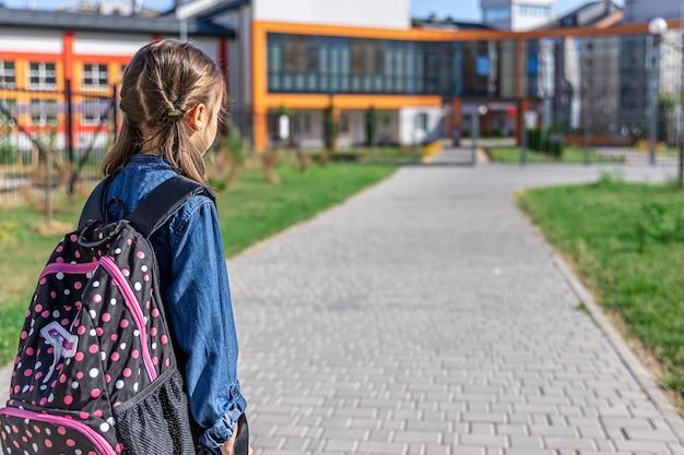 Маленькая девочка ходит в начальную школу. ребенок с рюкзаком собирается учиться. снова в школу концепции.