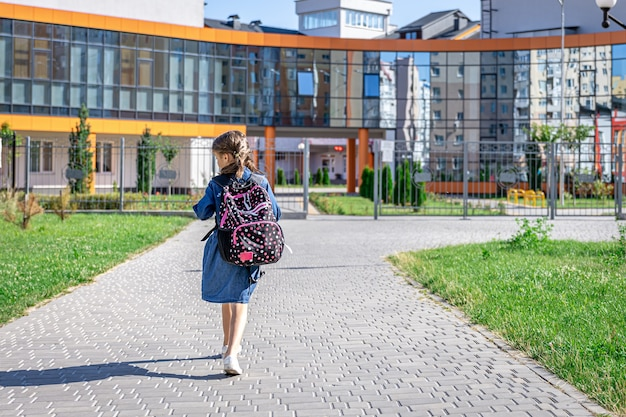 Маленькая девочка идет в начальную школу ребенок с рюкзаком собирается учиться