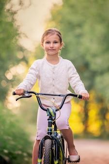 어린 소녀는 일몰 자연 속에서 시골 도로에 자전거와 함께 간다