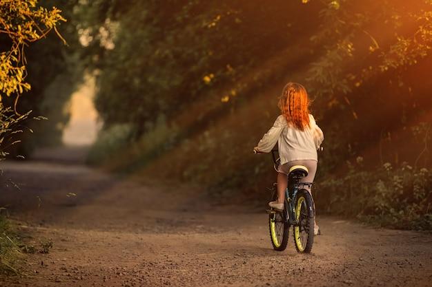 Маленькая девочка идет с велосипедом по сельской дороге на природе на закате