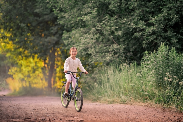Little girl goes with a bicycle on a rural road in nature at sunset