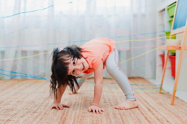 ロープの網を通過する少女