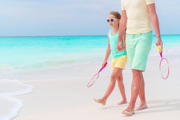 白い熱帯のビーチで父親と一緒にテニスをするつもりの少女