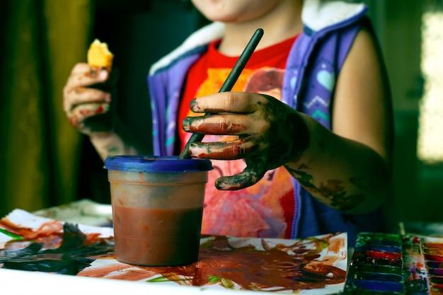 水彩で汚れた少女。カラフルな塗料でペイントすることを学ぶ子供