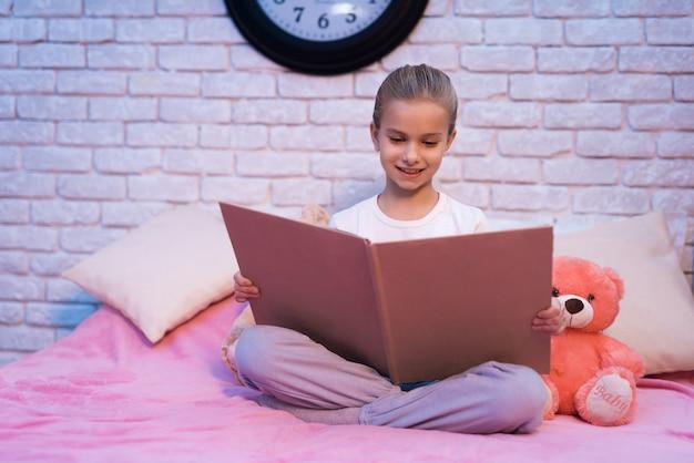 小さな女の子、孫娘が家で夜に本を読んでいます。 Premium写真