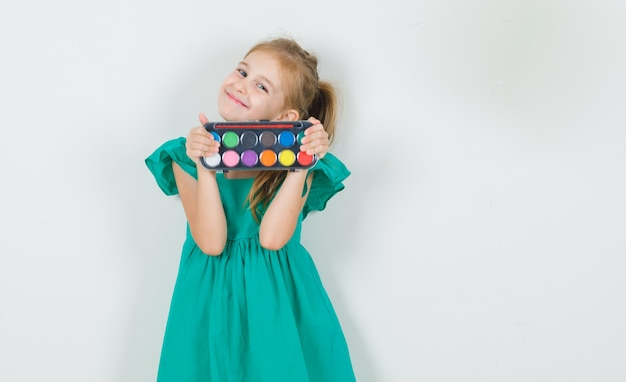 Little girl in green dress holding watercolor paints with brush and looking cheerful