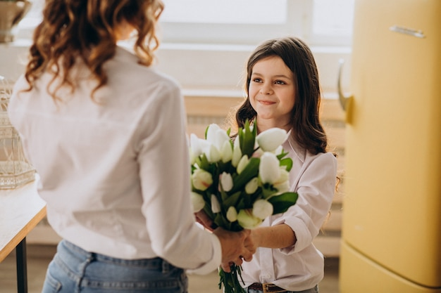Little girl greeting mother with flowers on mothers day