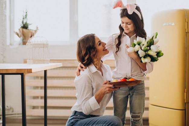 Маленькая девочка, приветствие матери с цветами на день матери