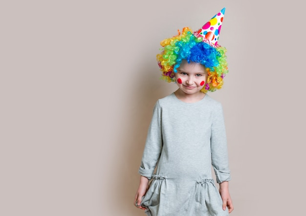 Little girl in grey dress and colourful wig