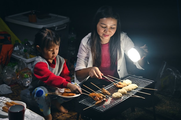 Little girl grill meat and hotdogs for dinner, at the camping with mother and family