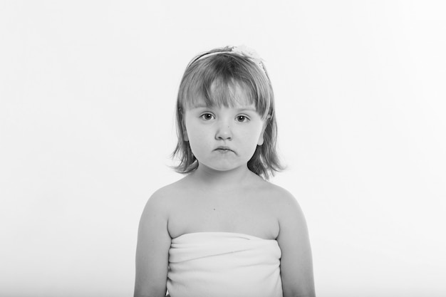 A little girl grimaces against a white background.