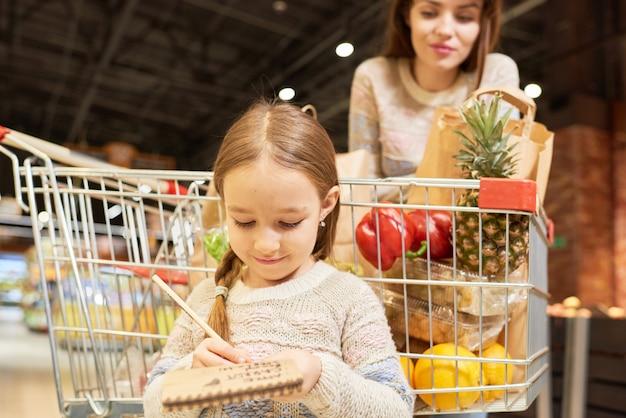 Маленькая девочка, делающая покупки с мамой
