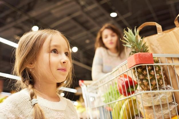 Маленькая девочка, делающая покупки с матерью