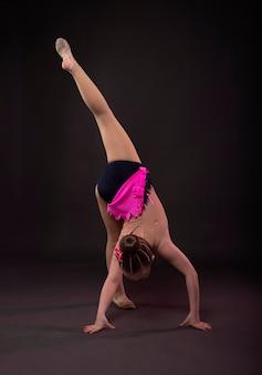 Little girl in gymnast in costume standing in handstand position in studio.