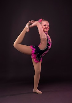 Little girl in gymnast in costume standing in position in studio, doing circle with leg and arm.