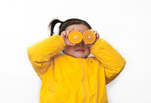 Little girl had an orange in her hand and put it on her eyes