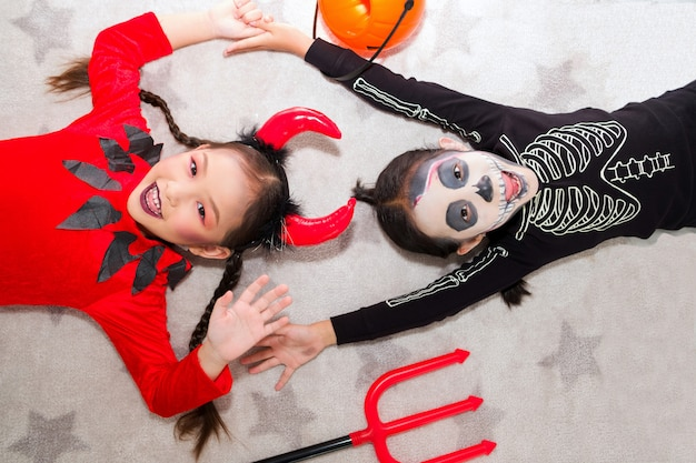 Little girl in halloween carnival costume with jack o lantern (pumpkin) and trident. asian cute children tease each other cheerfully.