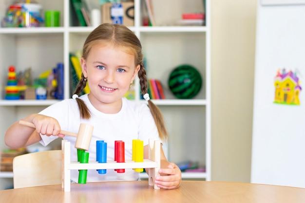 어린 소녀는 망치로 막대기를 망치. 손과 손가락의 발달.