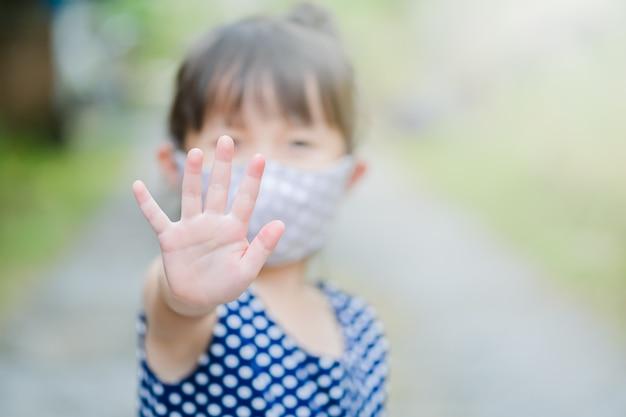 Маленькая девочка рука знак остановки и носить маску из ткани
