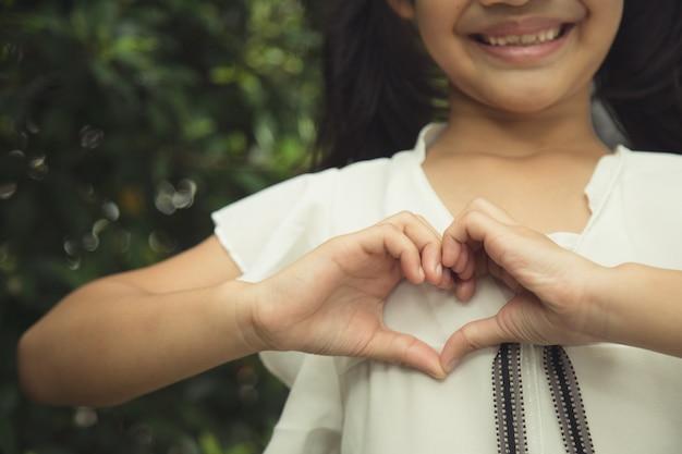 白い背景の上のハートの形を作る小さな女の子の手
