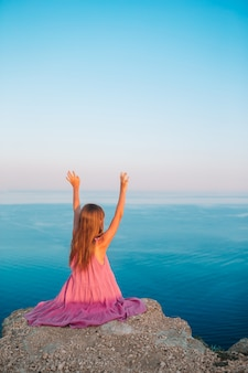 Little girl hands up on edge of cliff enjoy the view on mountain top rock