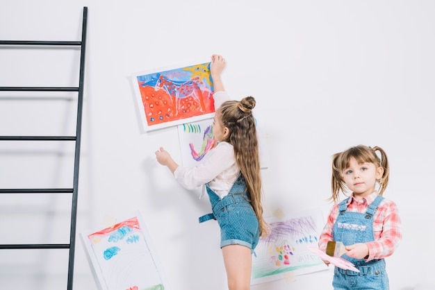 Little girl hanging drawings on wall
