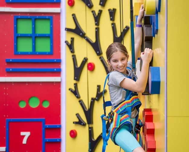 Маленькая девочка висит на трюмах на скалодроме