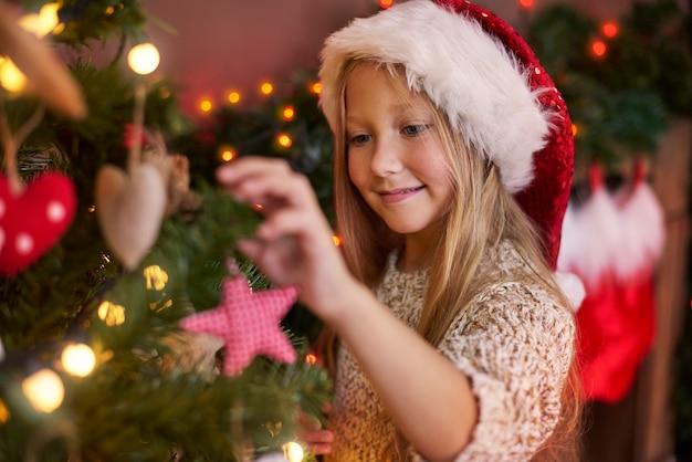 いくつかのクリスマスの飾りをぶら下げている少女